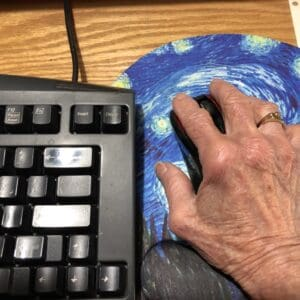 Keyboard beside hand on mouse